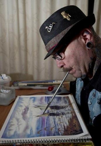 Свои картины он рисует кистью, которую держит ртом.