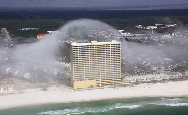 Многоэтажки, стоящие на побережье, из-за огромной высоты волн практически полностью «растворились» в столь необычных облачно-водяных массивах.